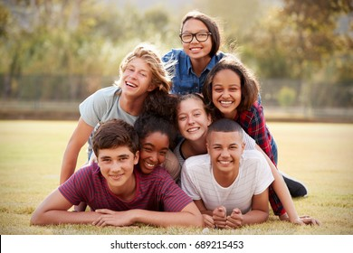 Group of teenage friends lying in a pile on grass