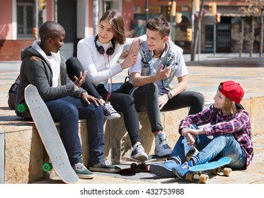 Group of teenage friends relaxing and chatting in town square
