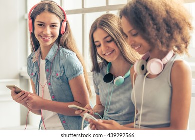 Group of teenage girls in headphones is listening to music using smartphones and smiling while sitting against window. One girl is looking at camera