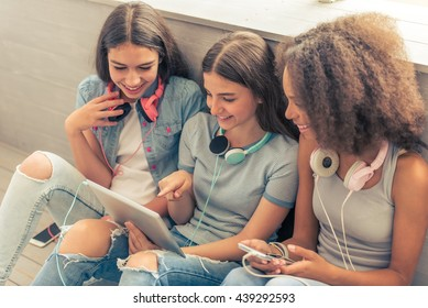 Group of teenage girls with headphones is using gadgets, talking and smiling while sitting on the floor