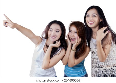 Group of teenage girls looks happy while pointing and looking at copy space in the studio
