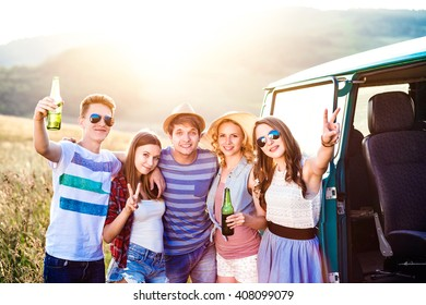 Group of teenage hipsters on a roadtrip, drinking beer