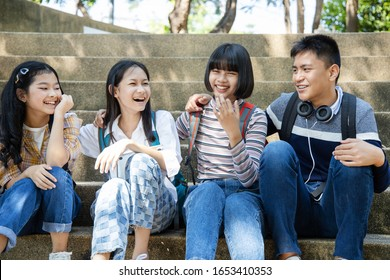 Group of teenage sitting in park and smiling.
