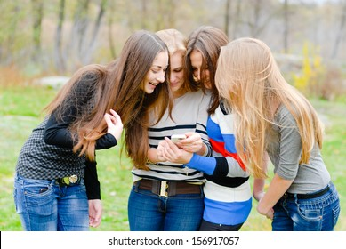 Group Of Teenage Students having fun using mobile phone on the spring or autumn outdoors background
