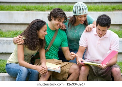 Group of Teenage students looking at work in folder outdoors