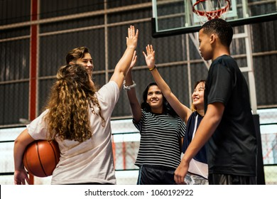 Group of teenager friends on a basketball court giving each other a high five