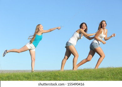 Group of teenager girls playing happy throwing water on the grass with the sky in the background