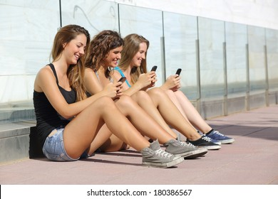 Group of teenager girls smiling happy texting on the smart phone sitting on the floor outdoors