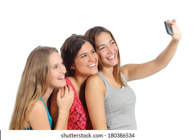 Group of teenager girls taking a photograph with the smart phone camera isolated on a white background