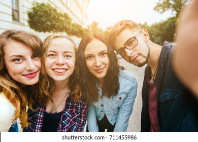 Group of teenager students doing selfie over the university building huggins, smiling, back to school concept. Sun glare effect. Four young happy student making selfie and smiling outdoors.