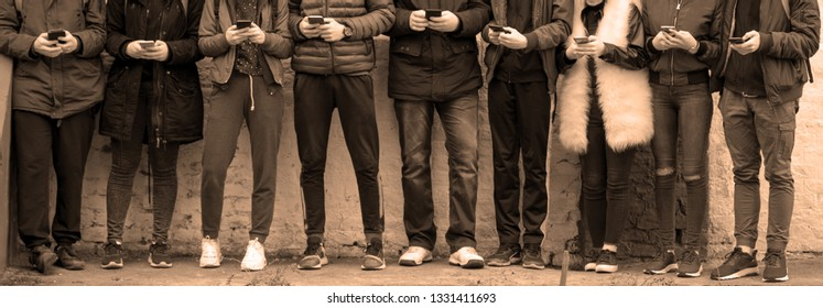 Group of teenagers with cell phones standing in front of wall and texting