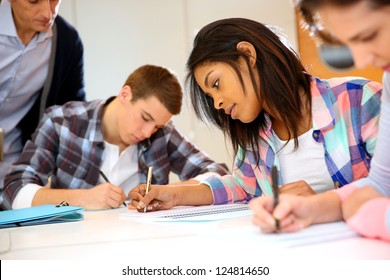 Group of teenagers in class writing an exam