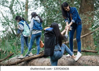 Group of teenagers college students giving helping hand up reaching out to help each other .