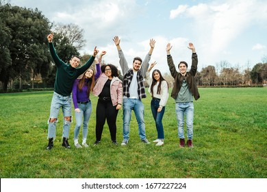 Group of teenagers of different cultures with your hands raised towards the sky at the park - Teamwork of young people - Six men and women having fun together