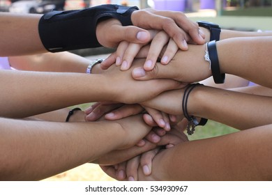 The group of teenagers with hands in stack, strong concept about teamwork and cooperation, also refers to immigration and friendship.