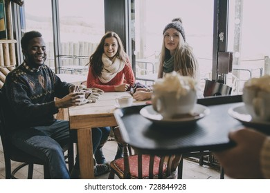 A group of teenagers happy to see their coffee being served in a cafe in winter.