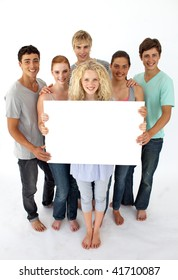 Group of teenagers holding a blank card agaisnt white background