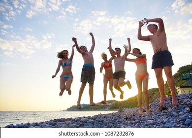 Group of teenagers jumpingon the beachr into the sea. fun summer vacation