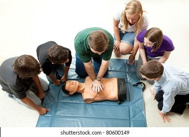 Group of teenagers learing CPR (cardiopulmonary resuscitation) in school.