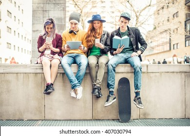 Group of teenagers making different activities sitting in an urban area - Friends hanging out outdoors