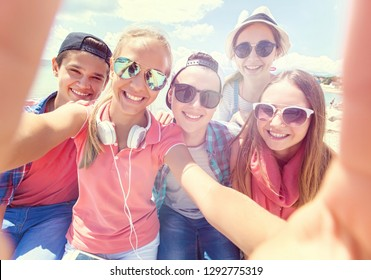 group of teenagers making fun selfie together
