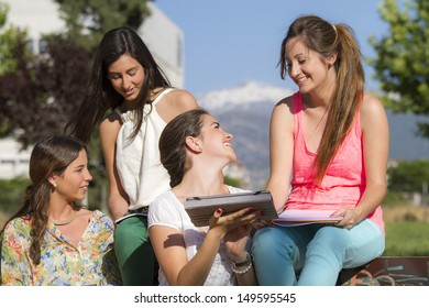 group of teenagers in a park doing there homework