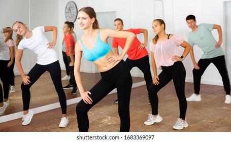 Grupo de adolescentes que participan en clases de danza, siguiendo a su joven profesora en la escuela de danza