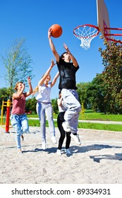 Group of teenagers playing street basketball