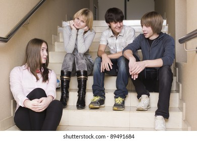 A group of teenagers sit on the steps