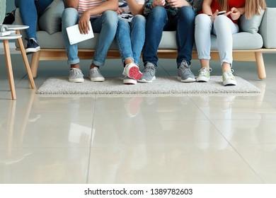 Group of teenagers sitting on sofa indoors