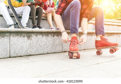 Group of teenagers sitting on the stairs. Tying the roller skates lace up.