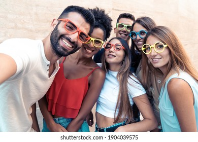 Group of teenagers taking a funny selfie wearing weird colorful sunglasses. Young people having fun using smart phones.