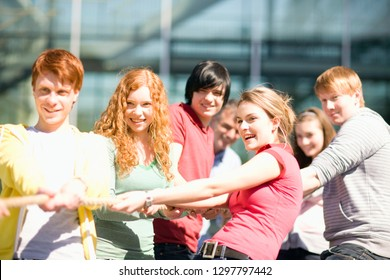 Group of teenagers in tug of war match pulling on rope outdoors