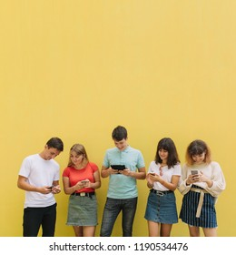 Group of teenagers using their mobile phones and tablet on a yellow background.