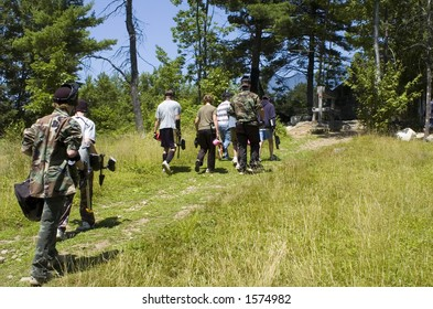 A group of teenagers walks up a hill toward a paintball course.
