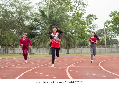 Group of teenagers wear sport cloth run on racetrack, jumping and exercise for health. Healthcare and sport concept. Free space for your text.