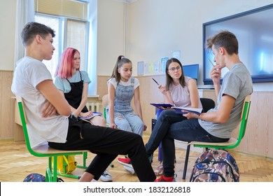 Group of teenagers with young female teacher at classroom, sitting talking discussing. Education, lesson, youth, teaching, school, college concept