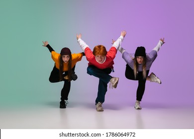 Group of teens, boys and girls dancing hip-hop in stylish clothes on colorful gradient studio background in neon light. Youth culture, movement, style and fashion, action. Fashionable portrait.