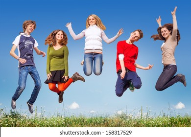 Group of teens jumping in the blue sky above the green grass