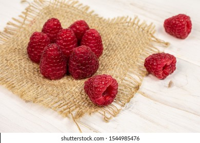 Group of ten whole fresh red raspberry on natural sackcloth on white wood