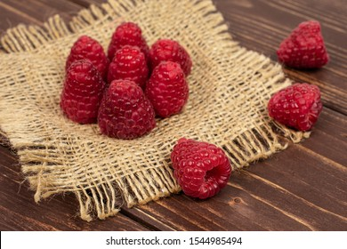 Group of ten whole fresh red raspberry on natural sackcloth on brown wood