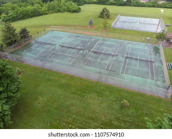 Group of tennis courts at park after summer rain
