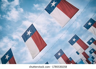 A group of Texas flags hanging against blue sky and white clouds.