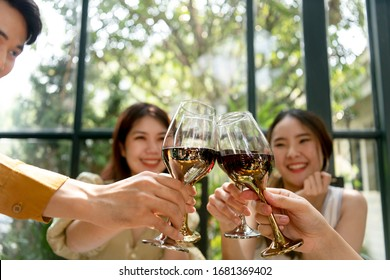 Group of thai asian friends toasting cheers with wine glasses. Celebrating friendshop and togetherness.