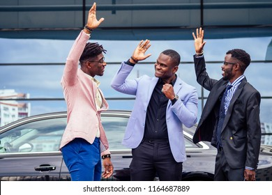 a group of their three successful African American businessmen in a stylish suit talking and rejoicing on the street skyscraper window background. teamwork and success concept