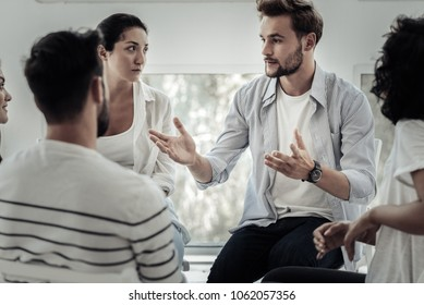 Group therapist. Nice pleasant young man looking at the group members and speaking to them while telling his story