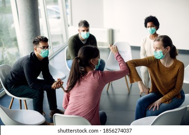 Group therapy participants elbow bumping and wearing face masks due to coronavirus pandemic.