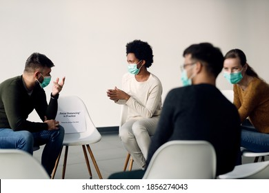 Group therapy participants talking while wearing face masks due to coronavirus pandemic. Focus is on African American woman.