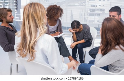 Group therapy session with one woman crying in therapists office