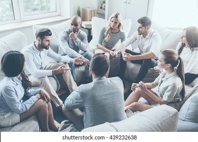 Group therapy. Group of young people sitting in circle while one man telling something and gesturing